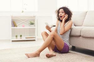 jovem negra em fones de ouvido com celular foto