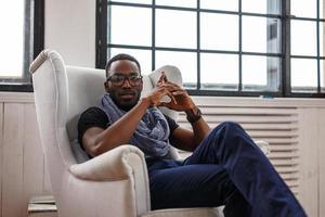 um homem negro relaxando em uma cadeira branca.