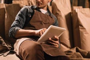 trabalhador de avental com tablet sentado no saco de saco