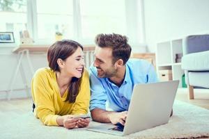 casal feliz em casa pagando com cartão de crédito para compras on-line foto