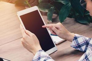 mulher asiática usando tablet na mesa de café foto