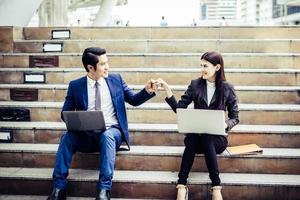 jovem casal de negócios sentado na escada, trabalhando alguns antes de ir trabalhar no laptop. foto