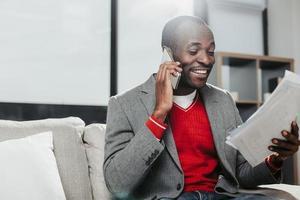 empresário satisfeito usando o gadget e olhando para documentos