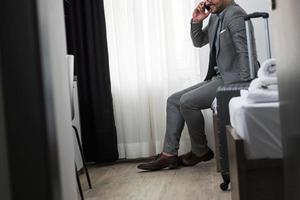 empresário usando telefone inteligente no quarto de hotel foto