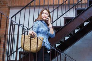 feliz asiática jovem atraente indo às compras descendo as escadas de uma praça de compras enquanto fala com seu telefone inteligente