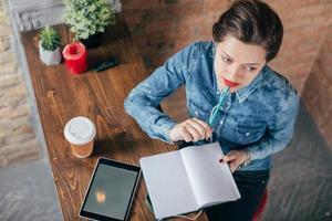 bela jovem freelancer feminino com bloco de notas e tablet tem uma pausa para café no quarto interior loft foto