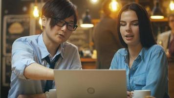 homem bonito asiático e bela jovem caucasiana, sentado no café trabalham em um computador laptop. em segundo plano outros clientes no ambiente elegante.