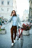 moda de bicicleta de homem. macho com bicicleta e telefone indo para o trabalho. foto