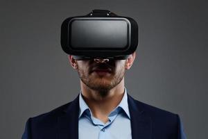macho de terno com óculos de realidade virtual na cabeça. foto