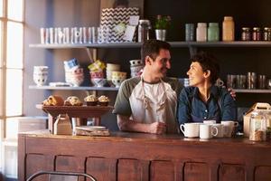 casal correndo café atrás do balcão foto
