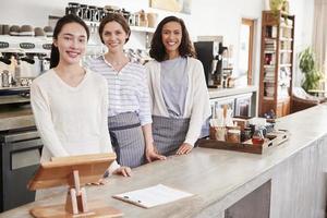 três donos de café feminino em pé atrás do balcão foto