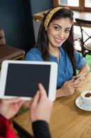 proprietário segurando o tablet enquanto mulher sentada à mesa na cafeteria foto