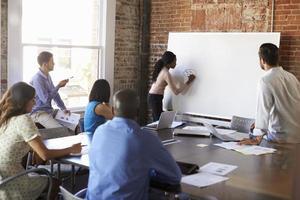 empresária no quadro branco na reunião de brainstorming foto