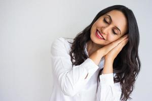 mulher bonita sorridente, fazendo o gesto do sono foto