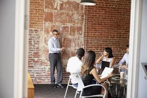 empresários reunidos na sala de reuniões moderna pela porta foto