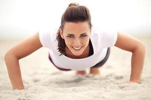 mulher na praia sorrindo enquanto fazendo push-up