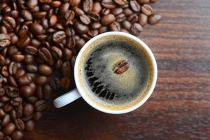 grãos de café em uma caneca branca sobre uma mesa foto