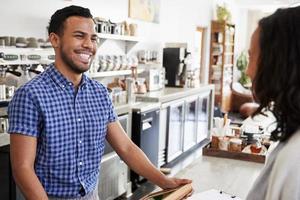 barista masculino sorri para um cliente feminino em uma cafeteria foto
