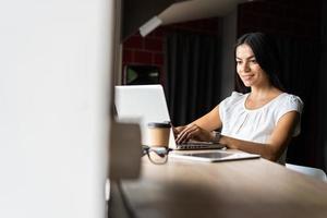 procurando por nova solução. empresária bonita jovem pensativa em copos trabalhando no laptop enquanto está sentado no seu local de trabalho