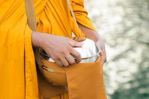 monge budista carregando uma tigela de esmolas foto