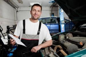 mecânico de automóveis, verificando o carro em serviço foto