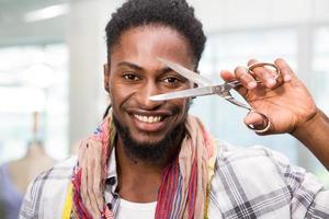 feliz designer de moda masculina, segurando uma tesoura foto
