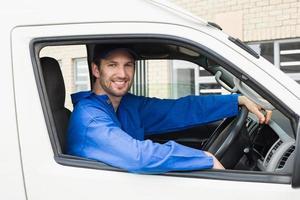 motorista de entrega sorrindo para a câmera em sua van
