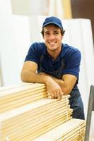 trabalhador de loja de ferragens ao lado de madeira empilhada foto