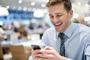 feliz jovem executivo sentado com smartphone foto