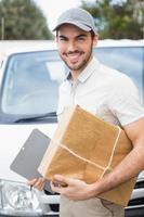 motorista de entrega sorrindo para a câmera por sua van