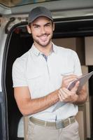 motorista de entrega sorrindo para a câmera ao lado de sua van