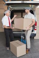 gerente de armazém e motorista de entrega falando ao lado de van