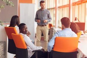 conceito de negócio, inicialização, apresentação, estratégia e pessoas - homem fazendo a apresentação à equipe criativa no escritório foto