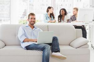 jovem designer sorridente, trabalhando em seu laptop no sofá foto