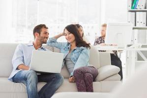 designers sorridentes trabalhando juntos no laptop no sofá foto