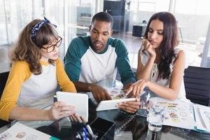 pessoas de negócios criativos discutindo sobre tablets digitais no escritório foto