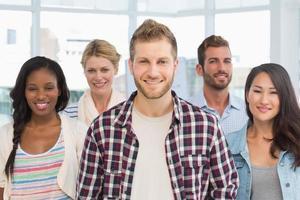 equipe de design diversificada em pé e sorrindo para a câmera foto