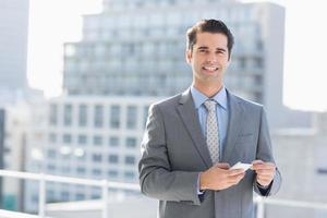mensagens de texto sorridente empresário com seu telefone móvel foto