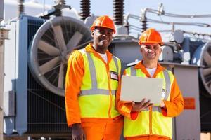 engenheiros eletricistas com laptop na frente do transformador foto