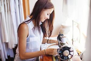 mulher sorridente bordando um vestido branco foto