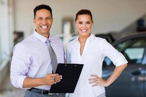 dois trabalhadores em pé dentro de carro showroom foto