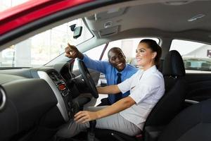 vendedor explicando as características do carro para o jovem cliente do sexo feminino foto