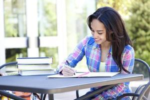 estudante étnico escrevendo e estudando com muitos livros foto