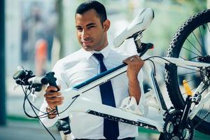 empregado de escritório bonito carregando sua bicicleta quebrada foto
