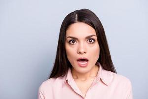 retrato de mulher chocada, assustada, com medo, impressionada, estressada e inesperada em camisa clássica com olhos de boca aberta, olhando para a câmera isolada em fundo cinza
