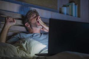 homem cansado e estressado atraente viciado em trabalho trabalhando tarde da noite exausto na cama ocupada com o computador portátil, bocejando, sentindo-se sonolento e sobrecarregado em conceito de estresse de prazo de projeto de negócios foto