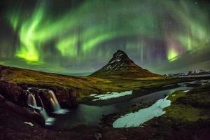 aurora boreal sobre mt. Kirkjufell na Islândia foto