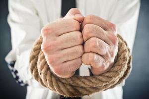 empresário com as mãos amarradas em cordas