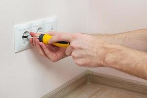 nas mãos de um eletricista instalando uma tomada na parede foto