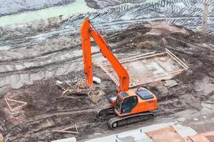 escavadeira laranja em um canteiro de obras